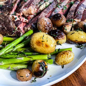 Close up shot of potatoes, asparagus, and steak on white plate.