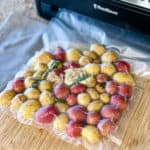 Little potatoes being vacuum sealed in plastic bag.