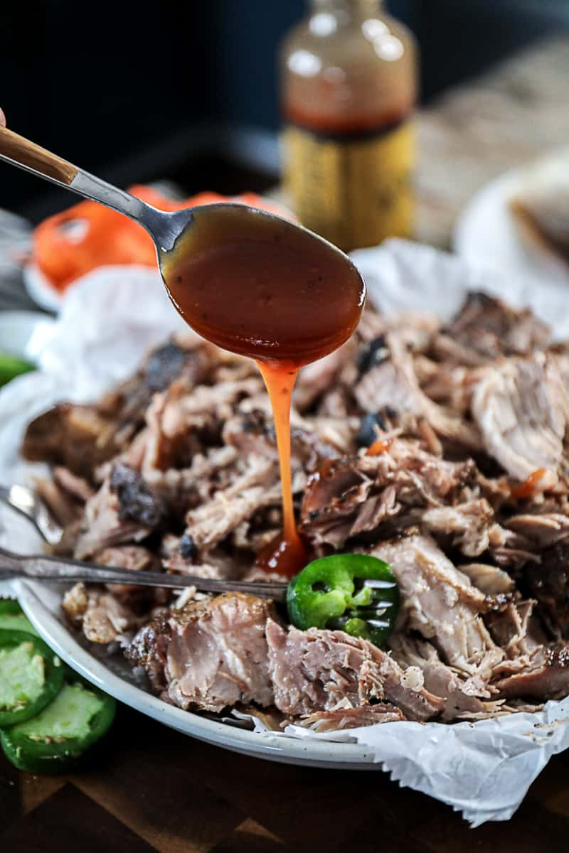 Spoon dripping barbecue sauce over shredded sous vide pulled pork on white plate.