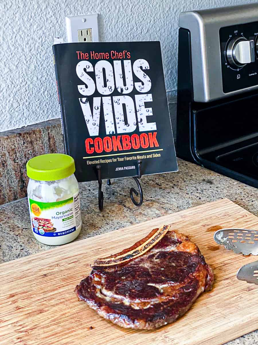 Sous vide ribeye steak on wooden cutting board next to cookbook display.