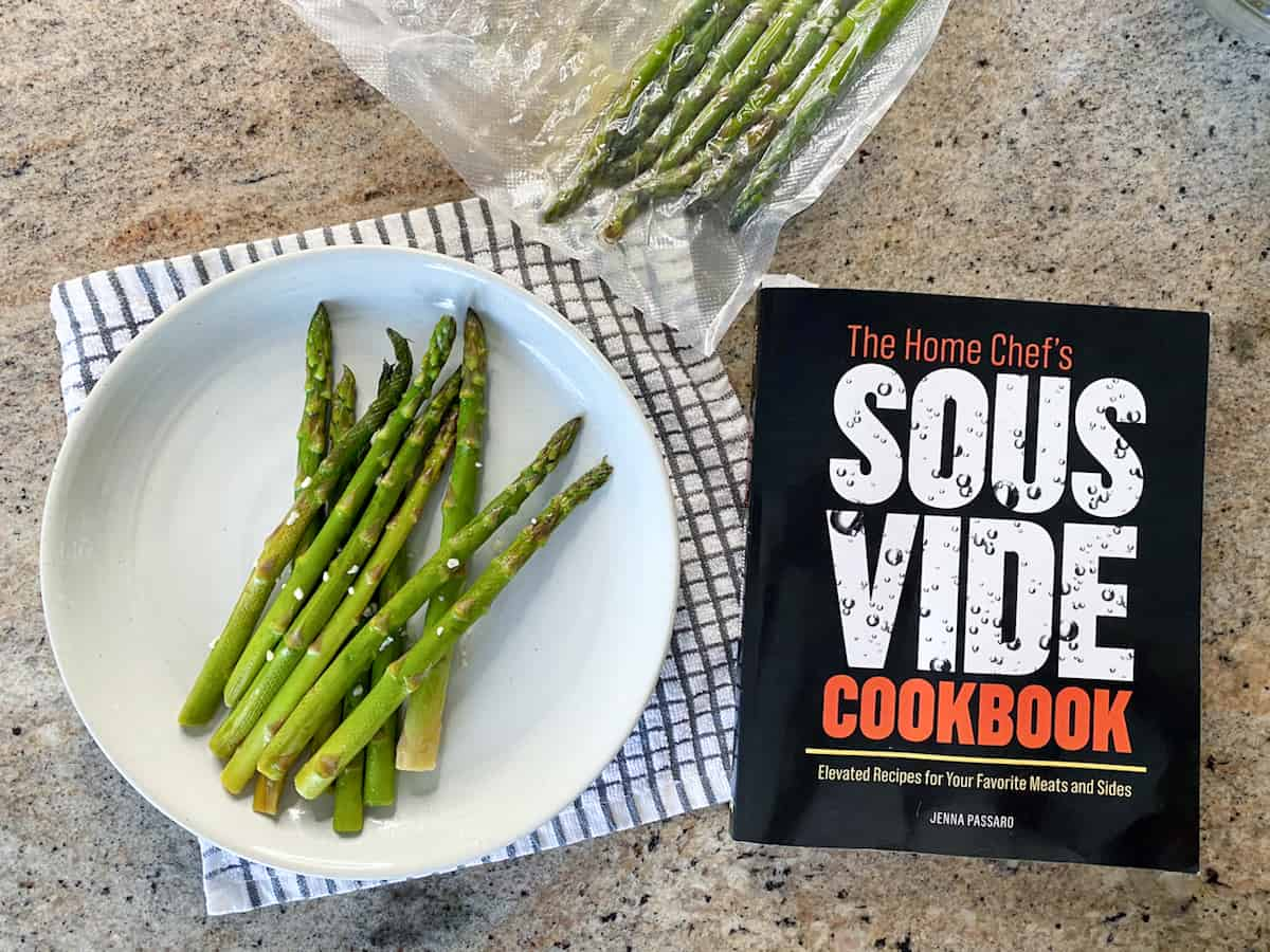 Top down shot of Instant Pot sous vide asparagus and the home chef's sous vide cookbook.
