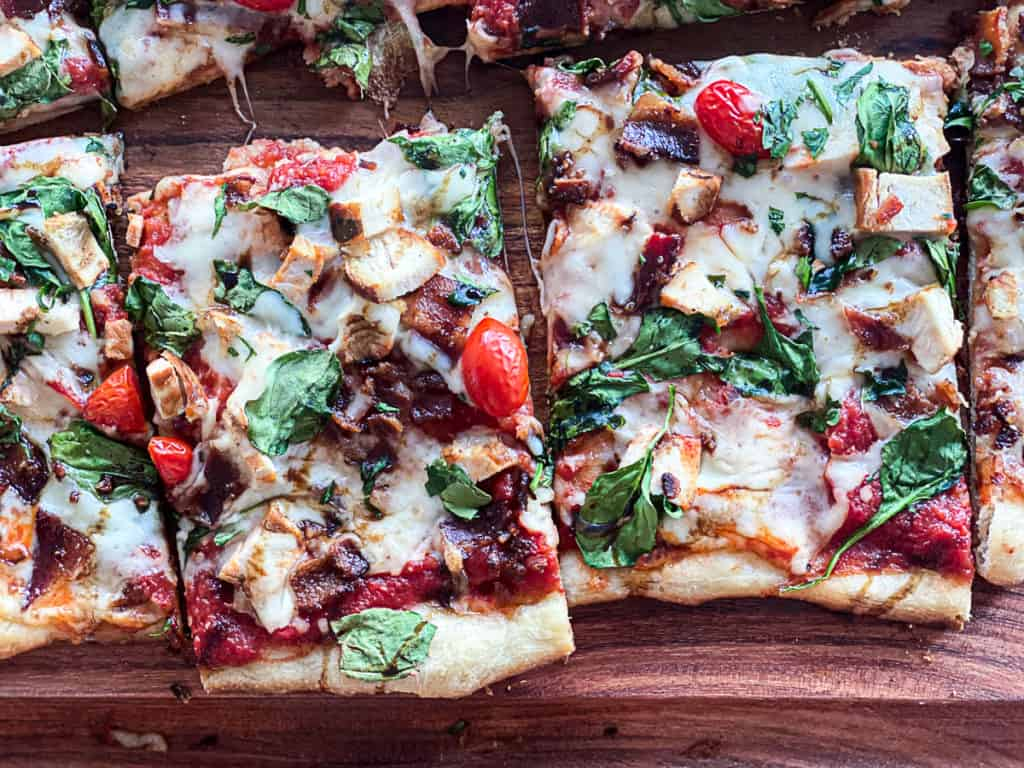 Top down shot of sliced chicken bacon spinach pizza with tomatoes and mozzarella cheese.