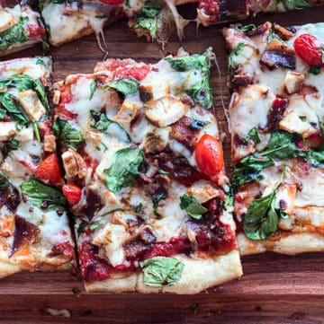 Closeup of chicken spinach pizza with bacon sliced on a cutting board.