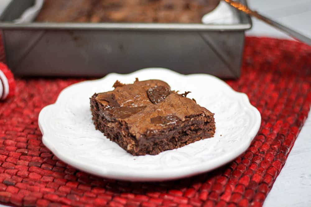 Side shot of chocolate chip brownie on a plate.