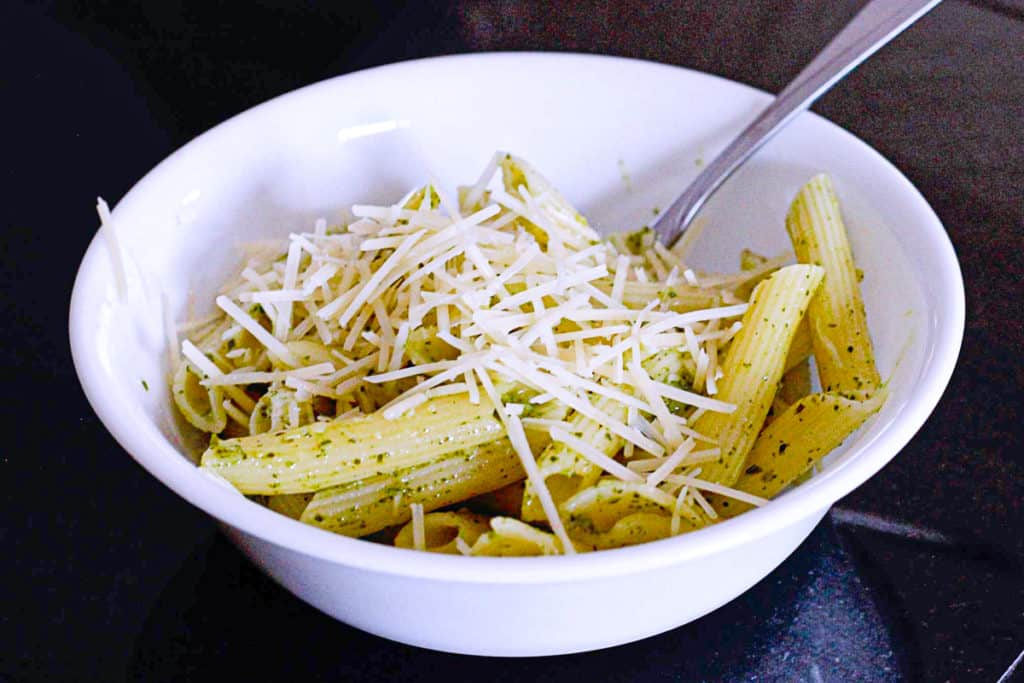 Side shot of pesto pasta with parmesan in a bowl.