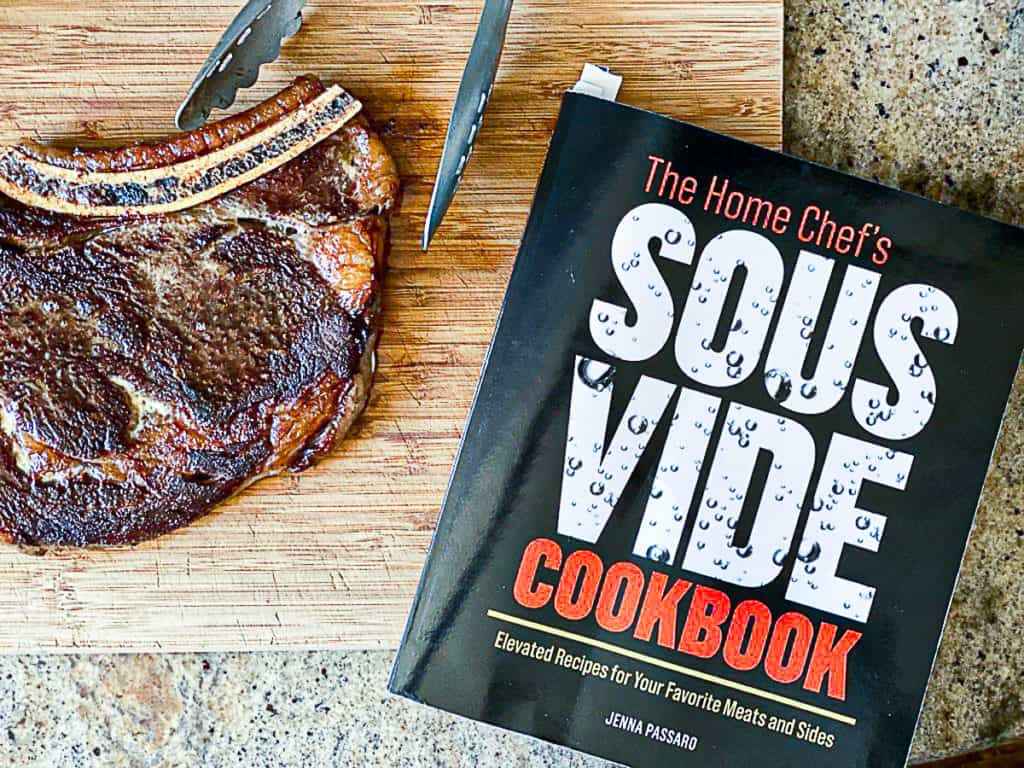 Top down shot of the home chef's sous vide cookbook and bone in ribeye steak.