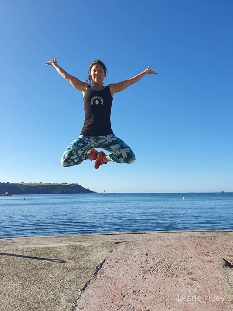 woman jumping in the air in front of a body of water