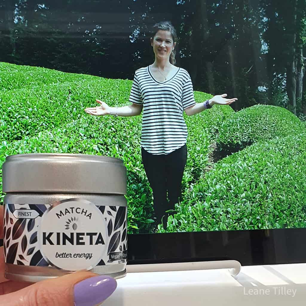 close up of hand holding a contatiner of matcha in front of a picture of a woman standing in greenery