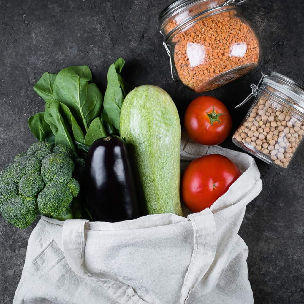 vegetables coming out of a canvas bag with beans in glass jars