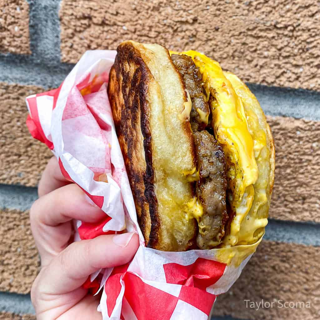close up of a hand holding a breakfast sandwich
