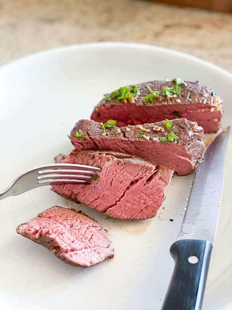 Sliced filet mignon steak on a white plate.