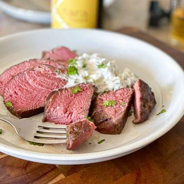 Side shot of fork holding medium rare sous vide steak.