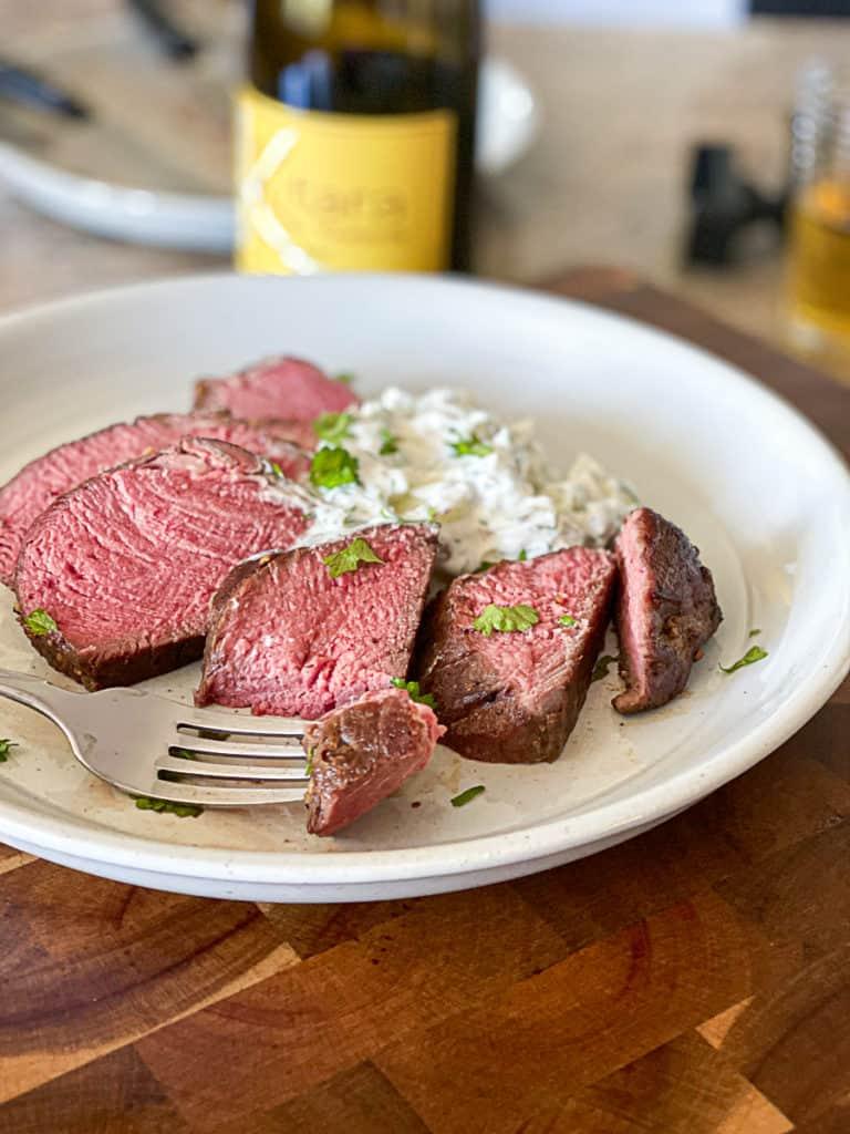 Medium rare sous vide steak with sauce.