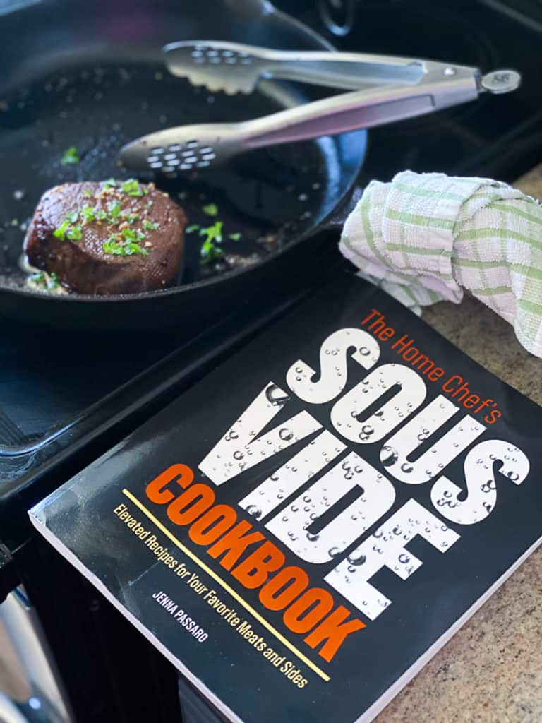 Top down shot of sous vide filet mignon with the home chef's sous vide cookbook.