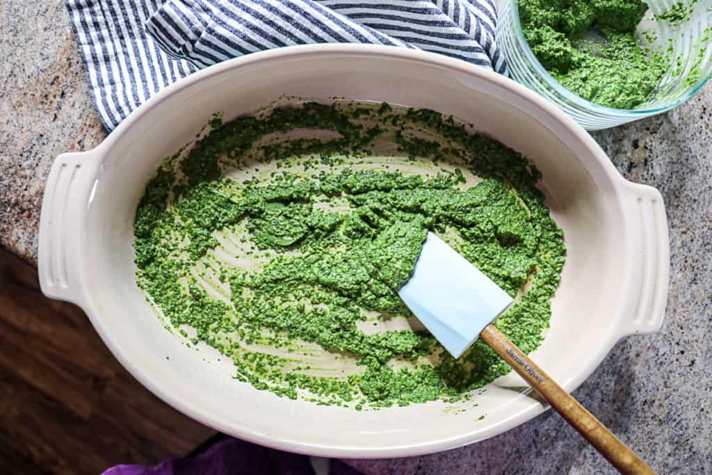 Top down shot of spatula spreading spinach pesto in lasagna casserole dish.