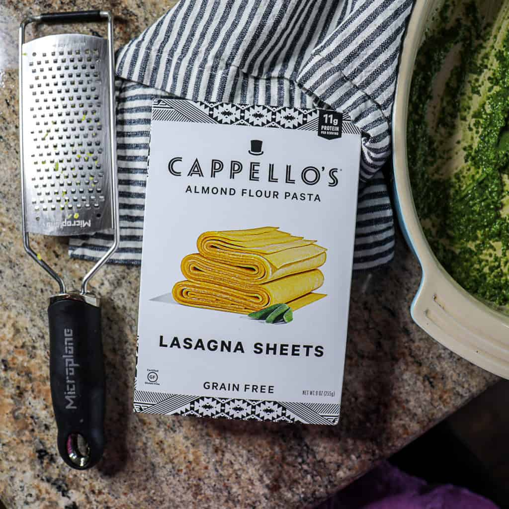 Top down shot of cappello's gluten free lasagna sheets and a cheese grater.