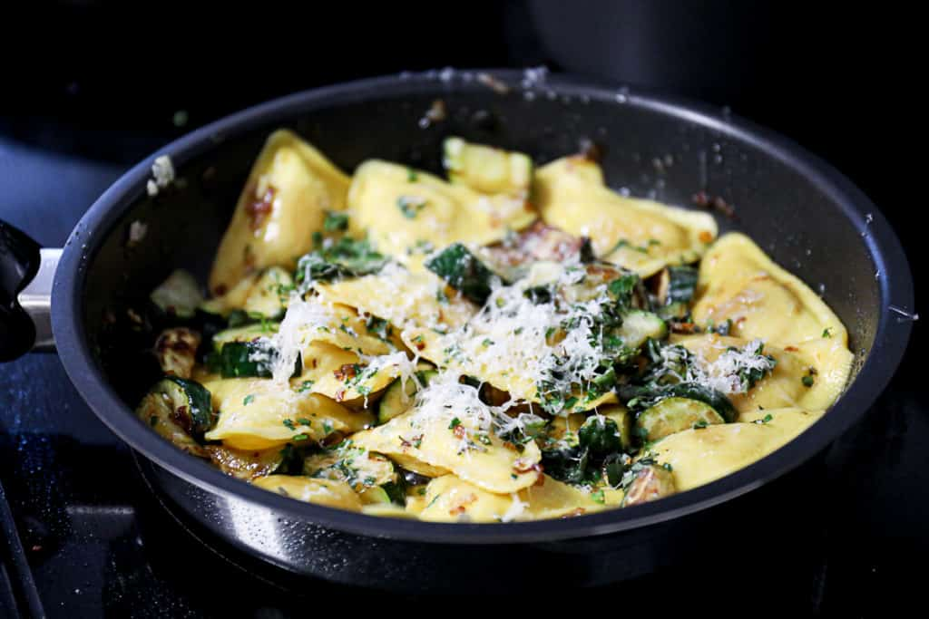 Side shot of parmesan cheese melting on butternut squash pasta with zucchini in a pan.