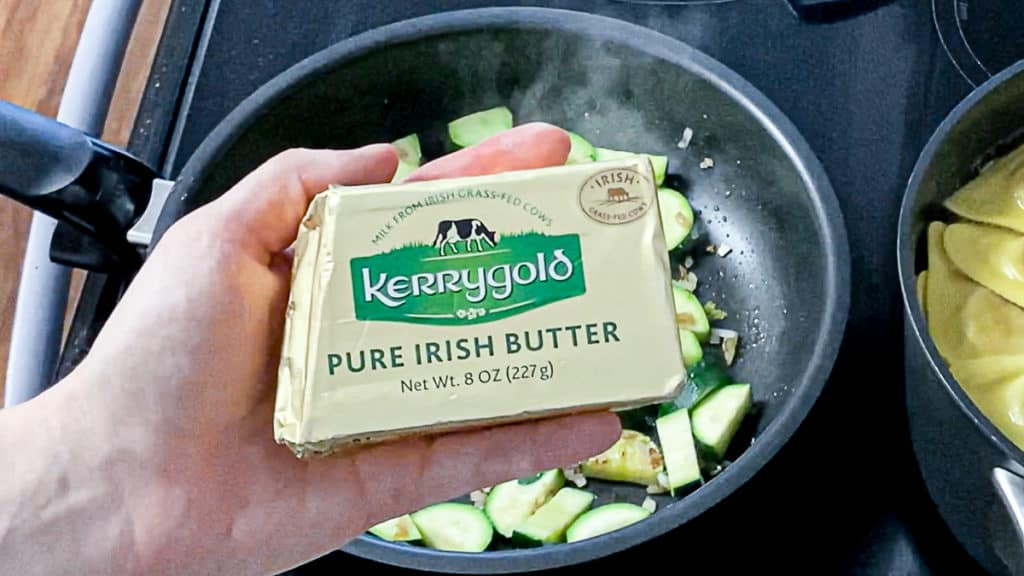 Top shot of hand holding Kerrygold butter over zucchinis cooked in a pan on the stove.