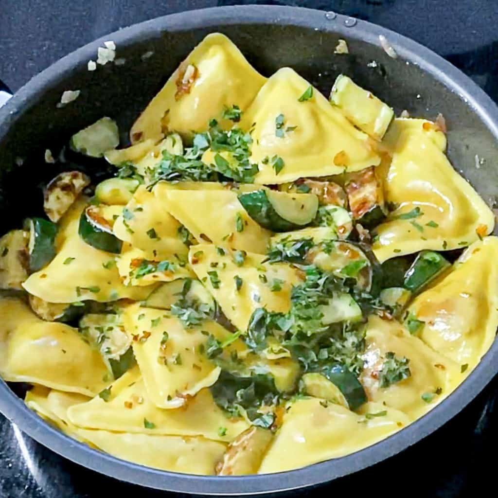 Top shot of cooking Trader Joe's Butternut Squash Ravioli With Zucchini and parsley in a pan.