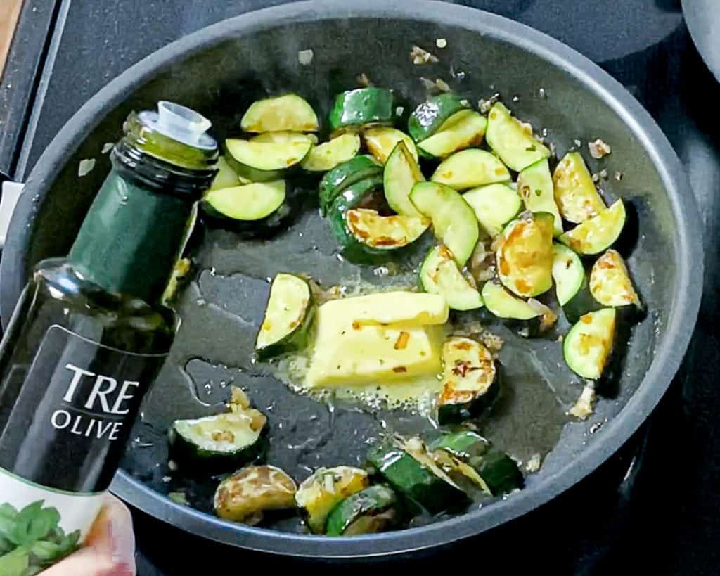 Top shot of zucchini frying in a pan with olive oil and butter.