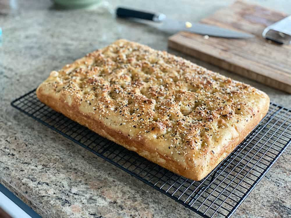 Side shot of baked focaccia bread with everything seasoning on a rack.