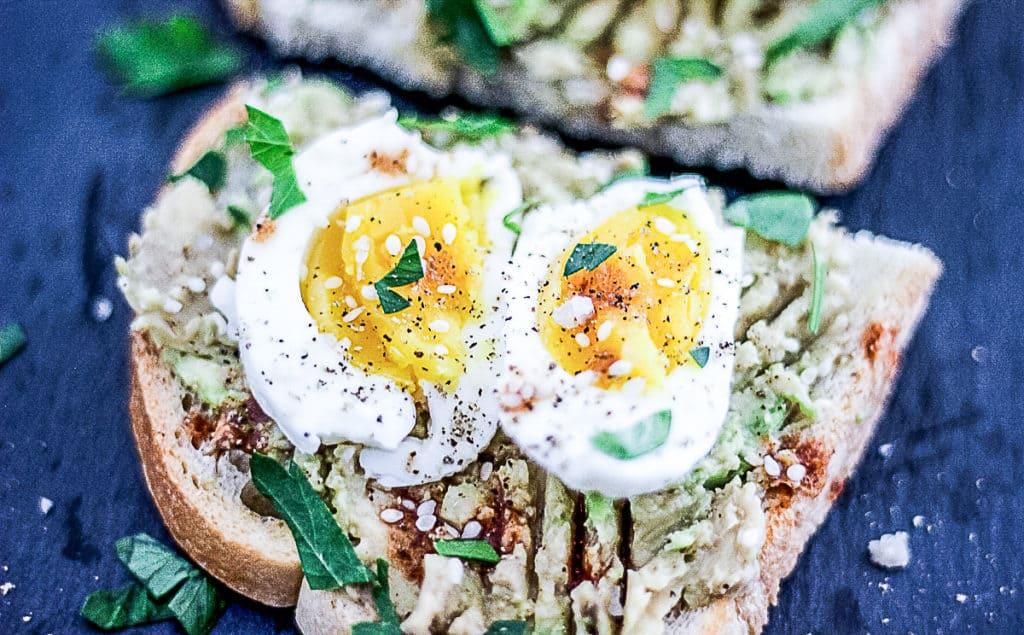 Closeup of sous vide soft boiled egg on avocado toast.