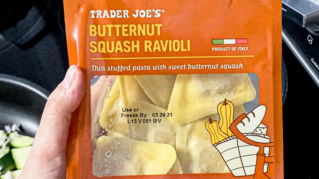 Top shot of hand holding a package of butternut squash ravioli from trader joe's brand.