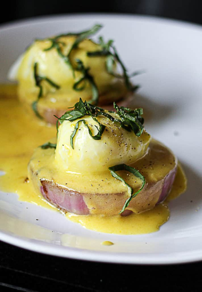 Closeup of sous vide poached eggs with hollandaise sauce on a plate with onion.