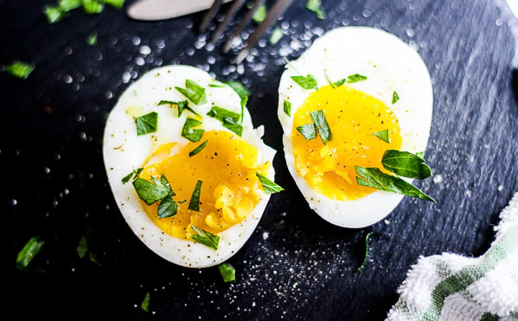 Closeup of sous vide boiled egg cut in half with herbs.