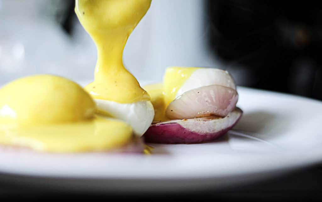 Drizzling hollandaise sauce on poached sous vide eggs.