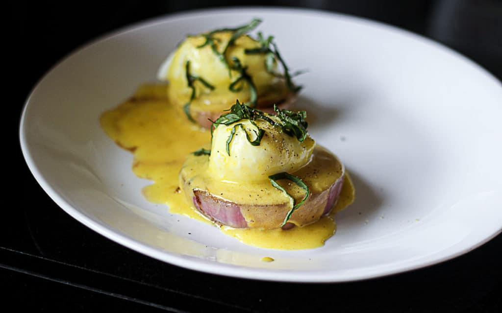 Side shot of sous vide eggs with hollandaise sauce on a plate.
