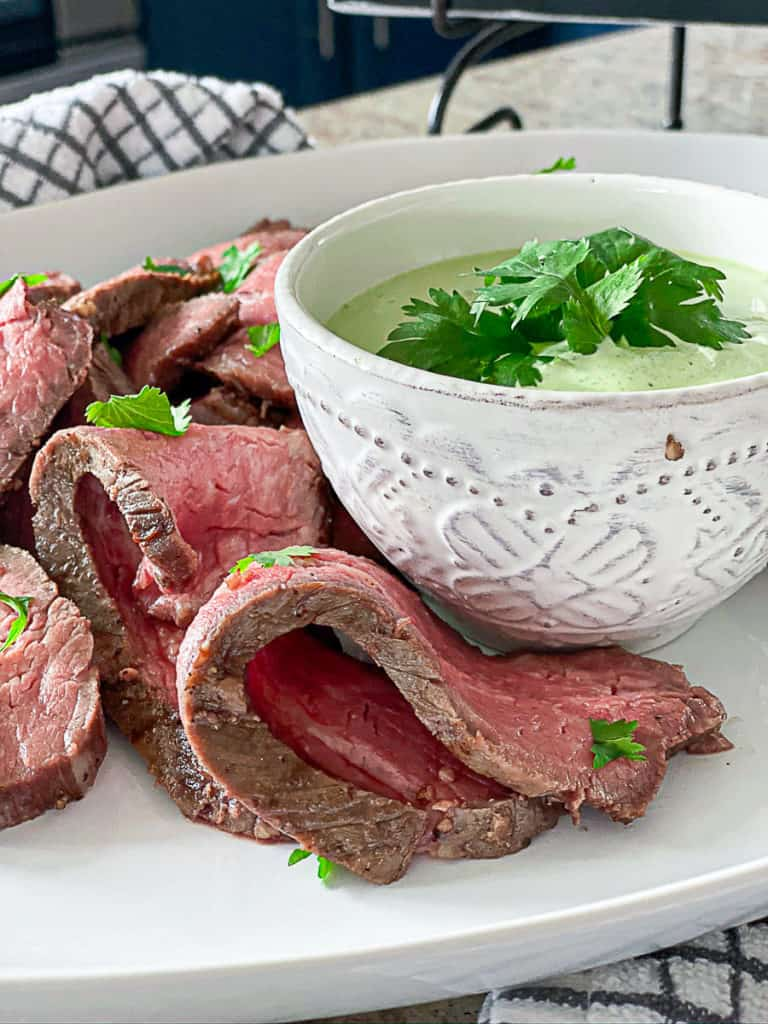 Side shot closeup of medium rare seasoned sous vide steak with sauce.