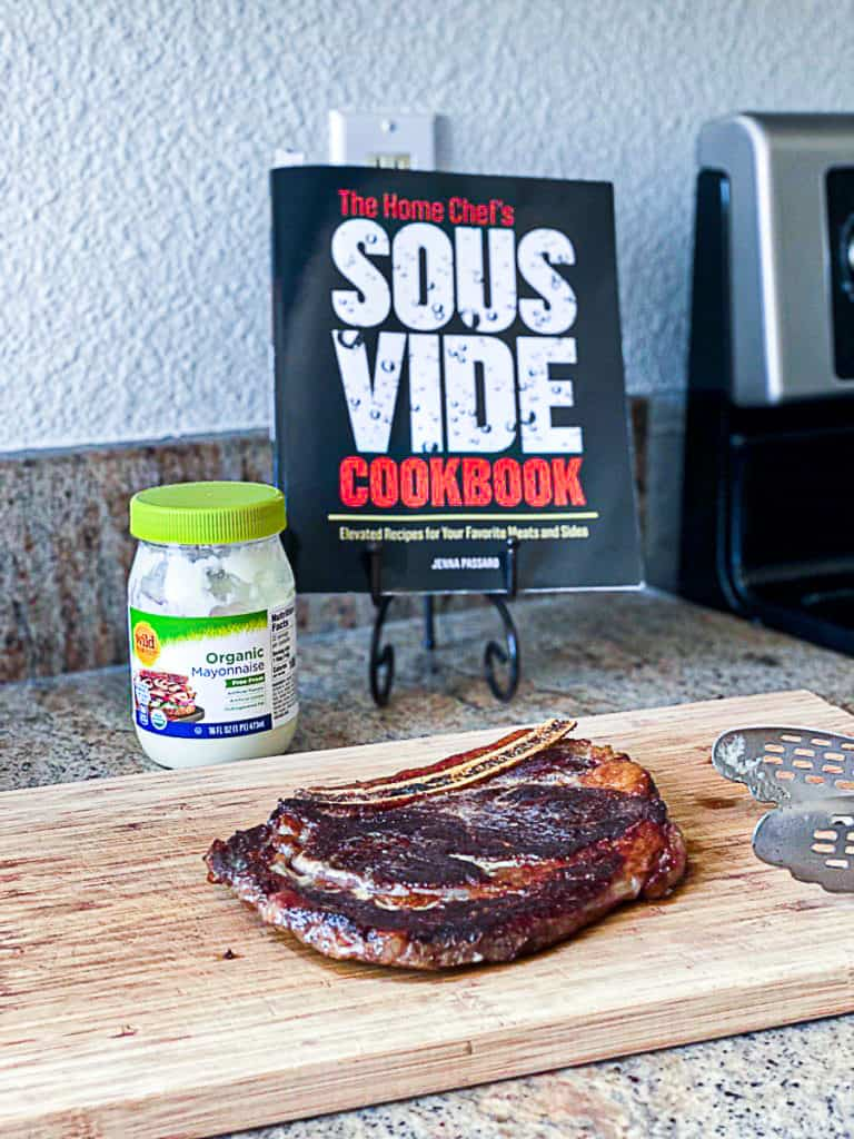 Side shot of sous vide ribeye steak mayo sear seasoning with the home chef's sous vide cookbook.