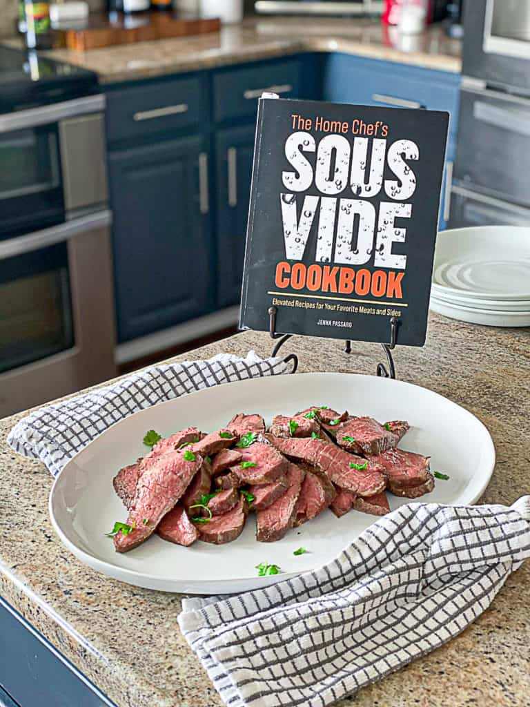 Side shot of the home chef's sous vide cookbook with sous vide steak seasoned with fresh herbs.