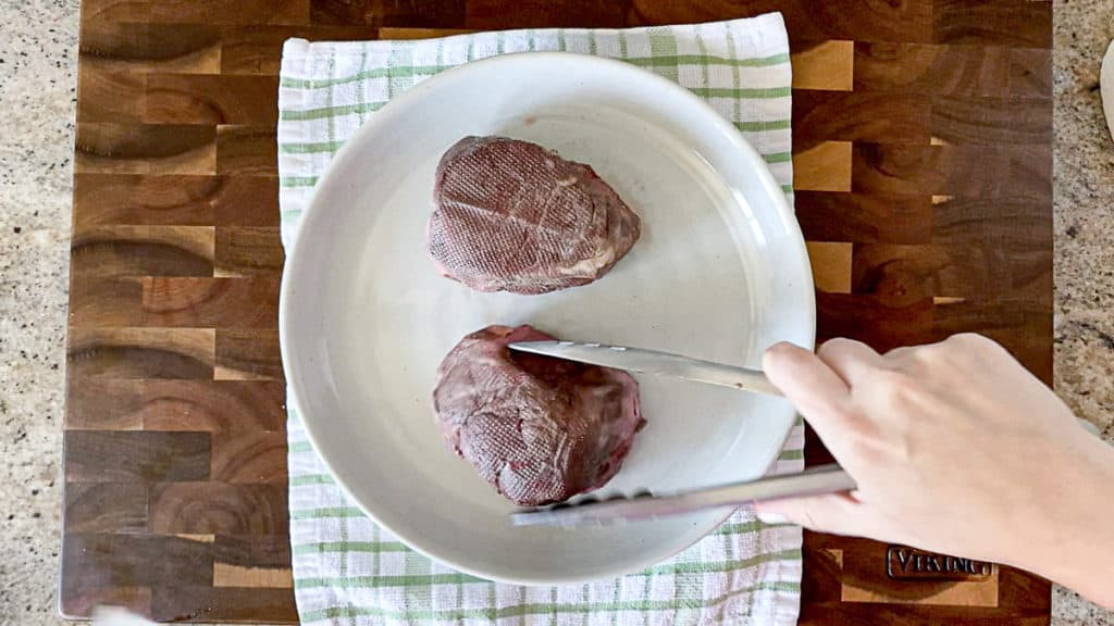 Fillet mignon being patted dry.