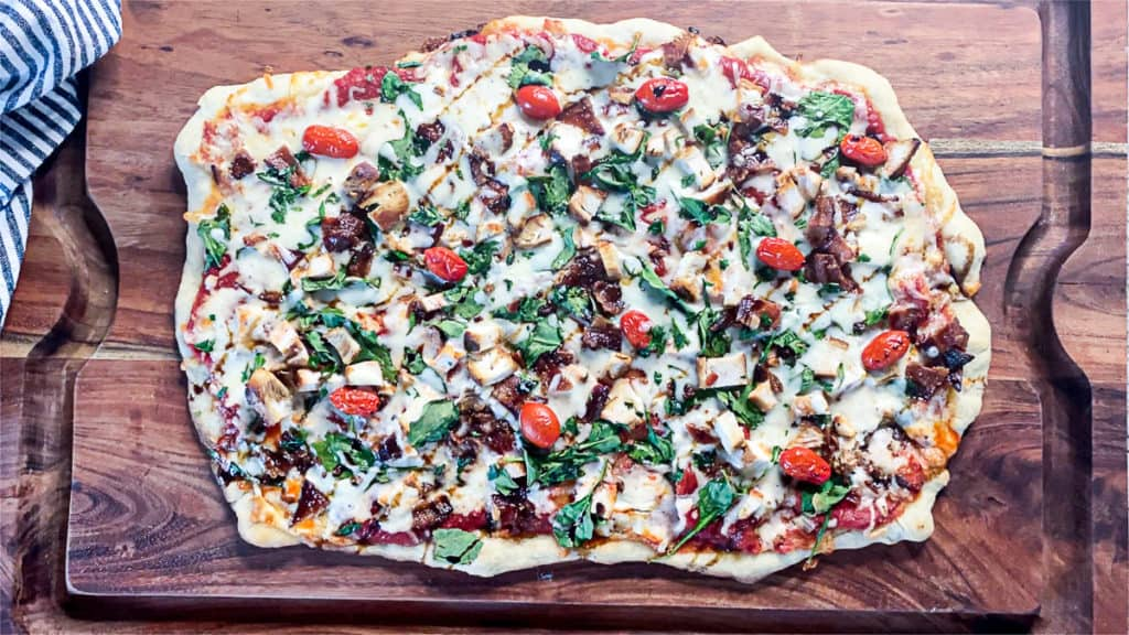 Top down shot of cooked chicken bacon spinach pizza.