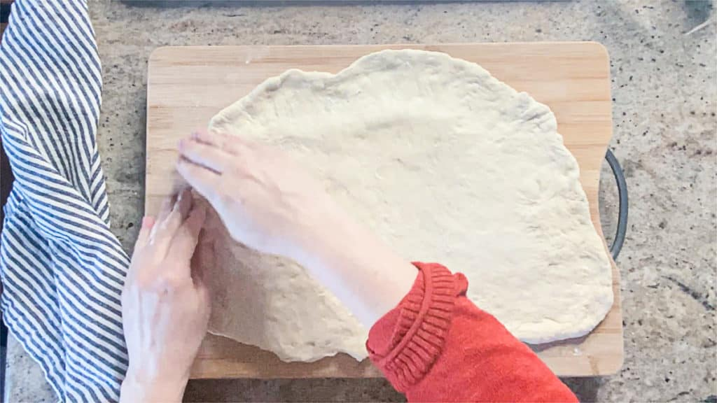 Top down shot of hands stretching ball of pizza dough on a counter.