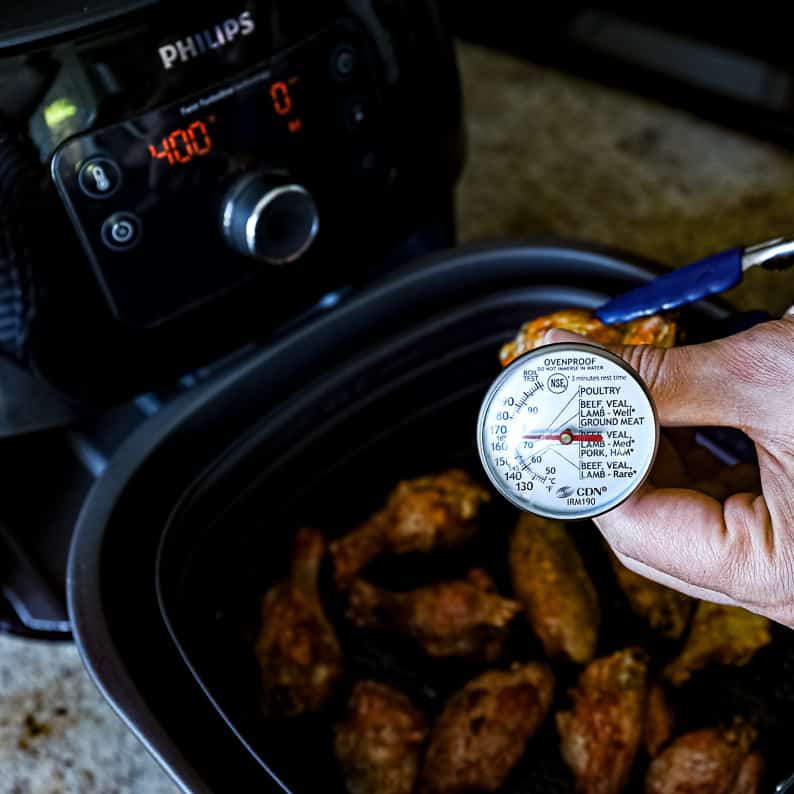 Top down shot of hands checking temperature for air fryer wings with thermometer.
