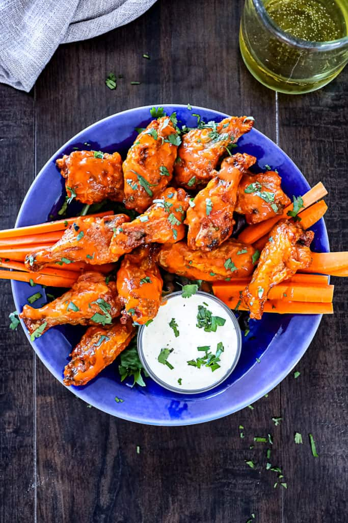 Top down shot showing finished cooking air fried chicken wings with buffalo sauce and blue cheese dressing.