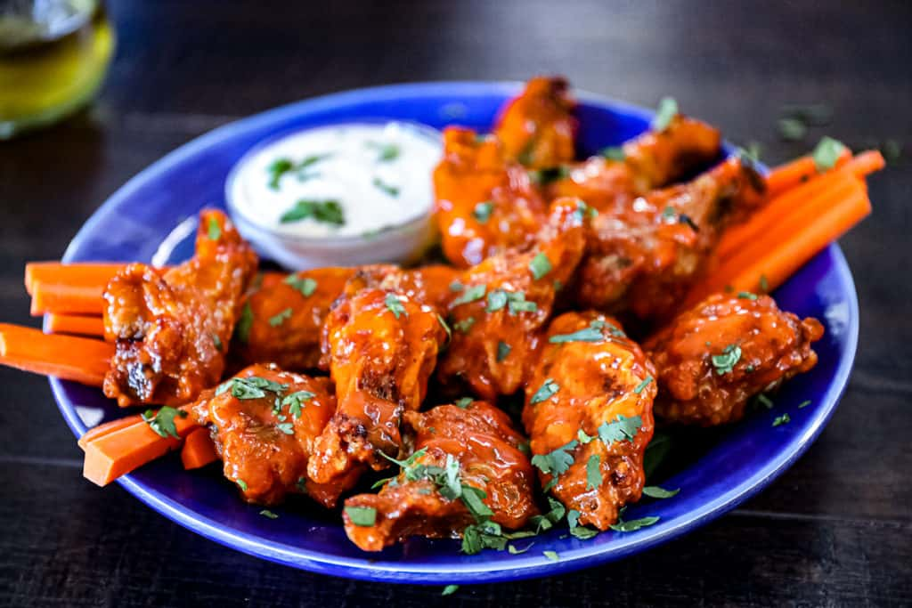 Closeup side shot of buffalo sauce air fryer wings served on a party platter.