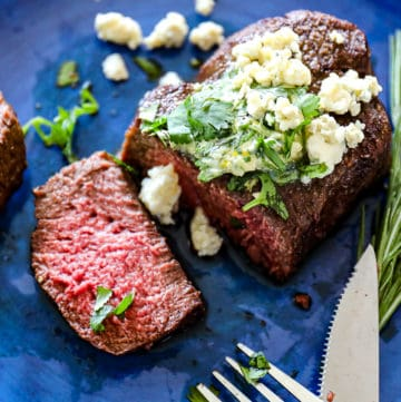 Side shot of sliced air fryer filet mignon steaks on a plate with compound butter and blue cheese garnish.
