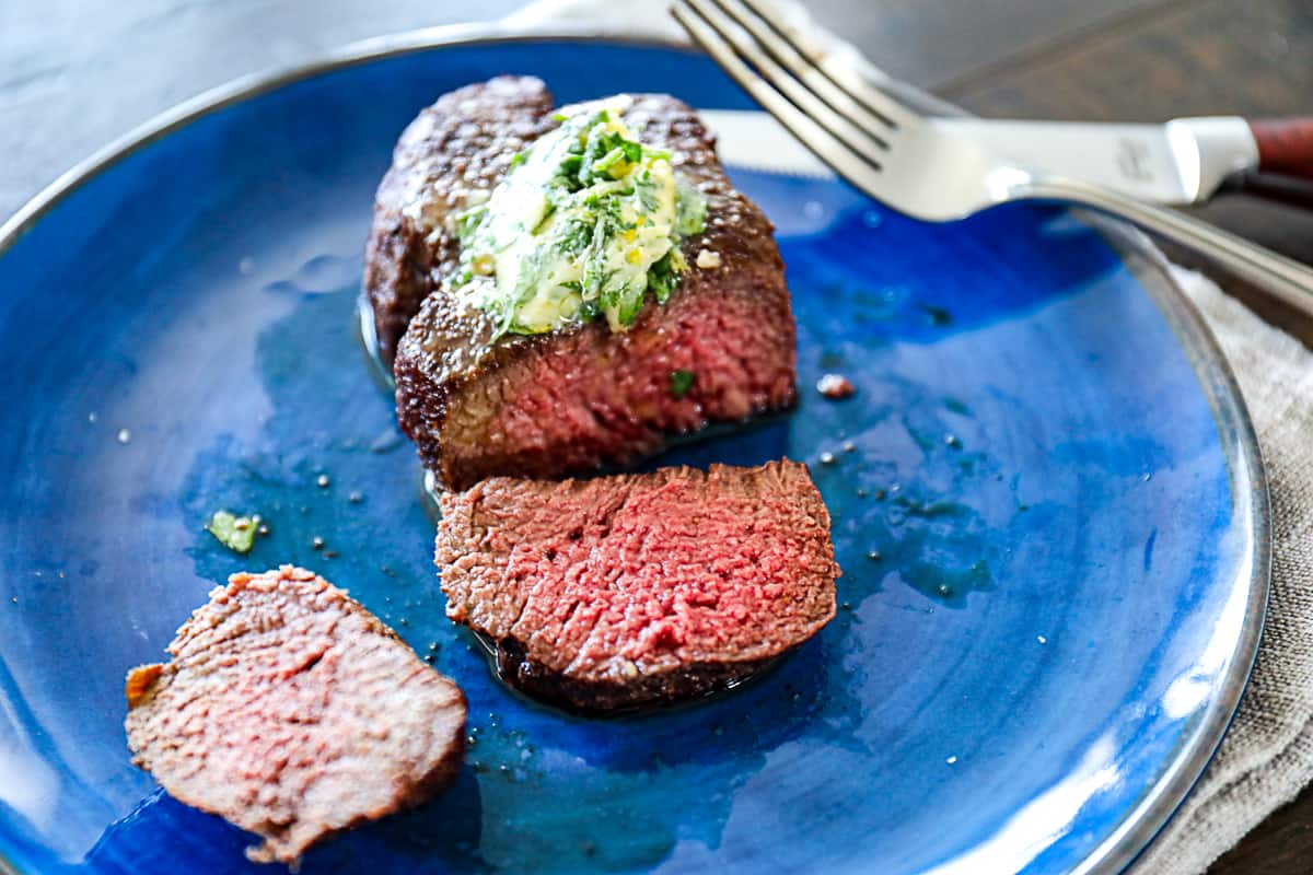 Side shot of sliced filet air fryer cooked with compound butter on a plate.