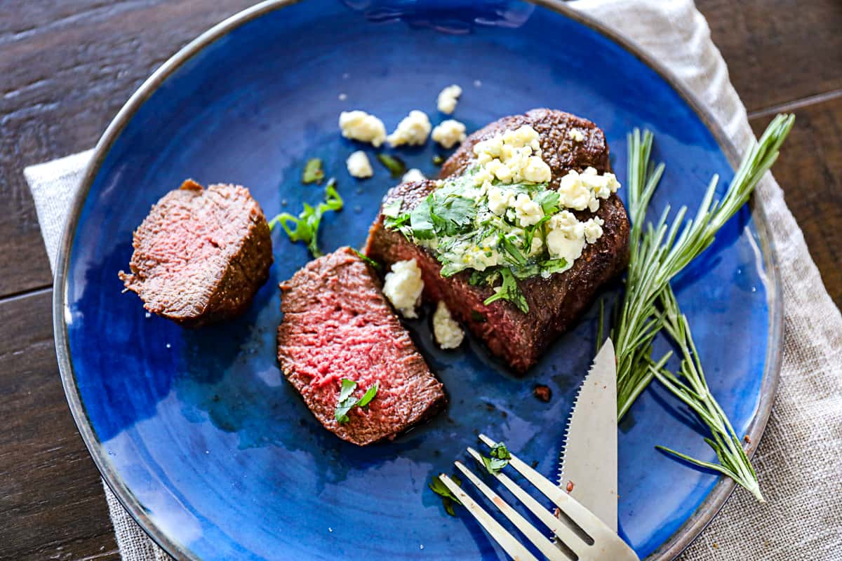 Sliced air fryer filet mignon steak with blue cheese and rosemary on a plate with utensils.