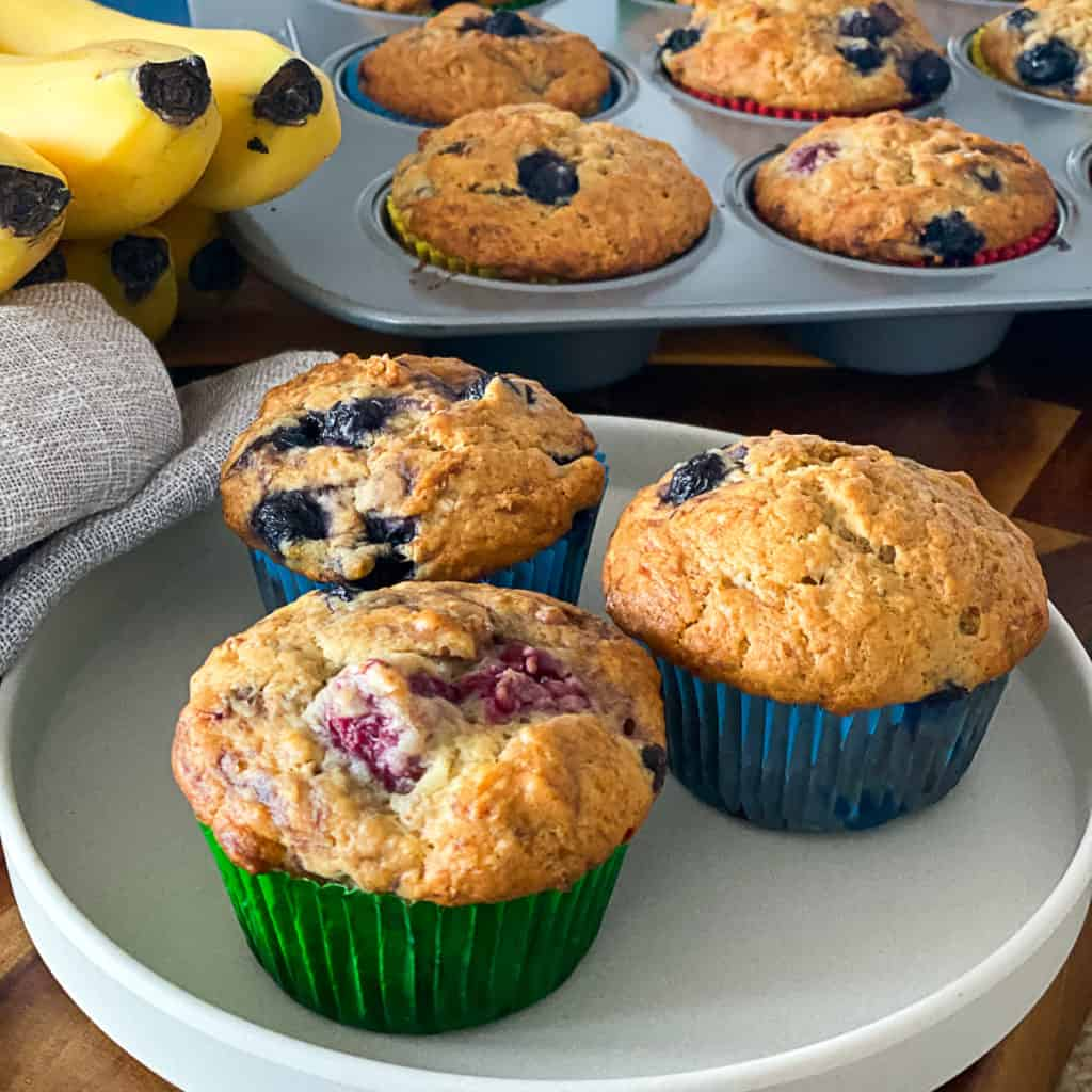 Closeup of banana blueberry muffins with frozen blueberries and raspberries.