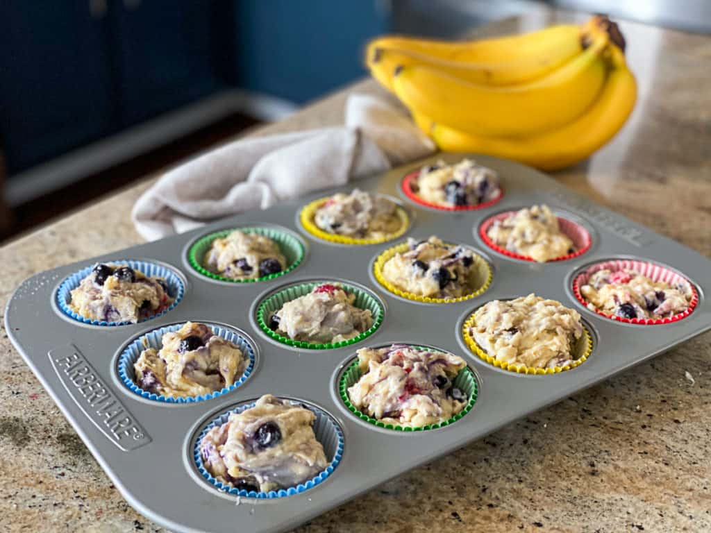 Side shot of wet muffin batter in muffin tin pan with ripe bananas on a counter.