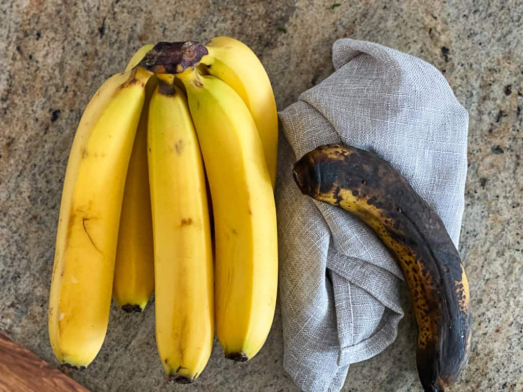 Top down shot of a bunch of yellow ripe bananas and an overripe banana that's brown.
