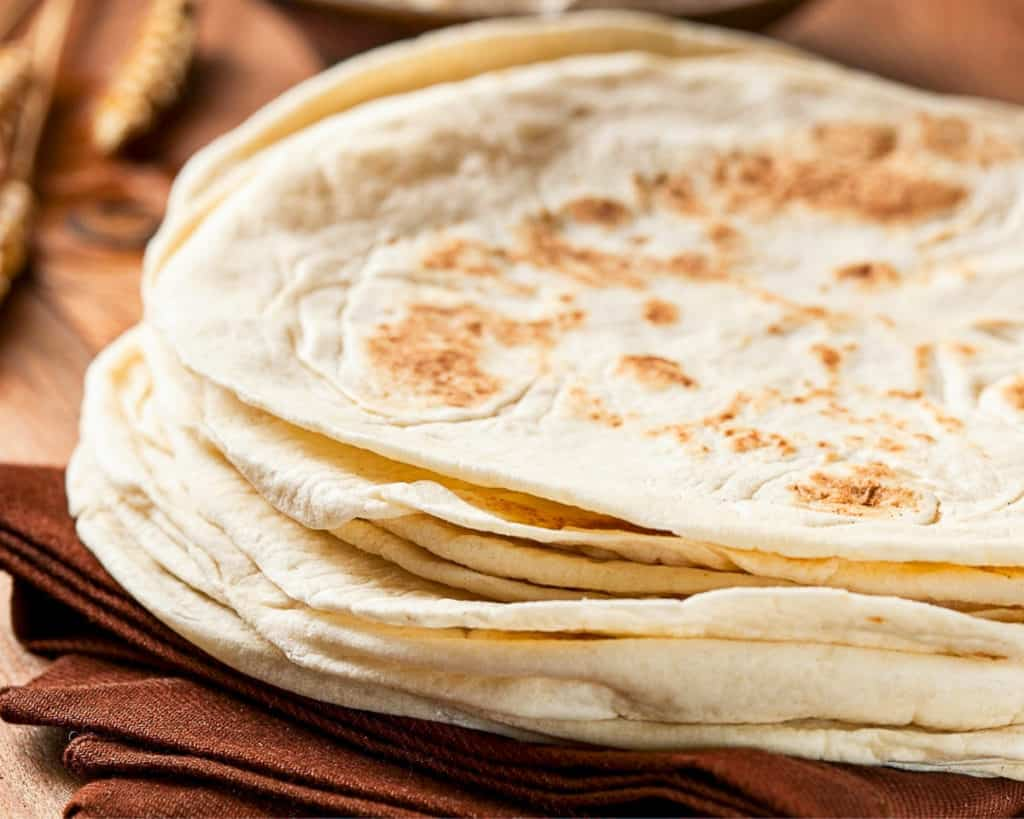 Side shot of flour tortilla stack on a table.