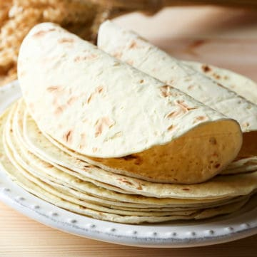 Side shot demonstrating thawed from frozen flour tortillas on a plate.