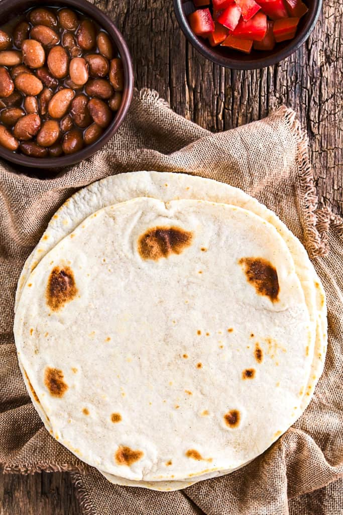 Top down shot of flour tortillas on a table.