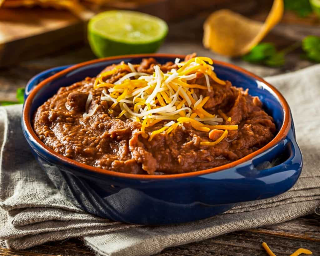 Bowl of refried bean dip with cheddar cheese.